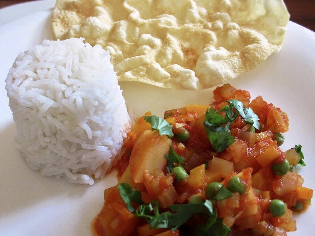 Curry van aardappelen, erwtjes en tomaten