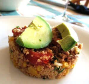 Salade van couscous met tonijn, mais en tomaat, met bovenop schijf avocado